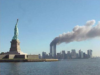 9/11 photo of the World Trade Center in flames, with the Statue of Liberty in the foreground.