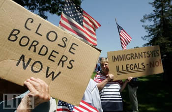 "Protesters with signs: ""Close borders now"" and ""Immigrants: yes; illegals: no""."