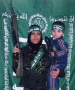 Female suicide bomber holding a child and a rifle; the child is holding a rocket-propelled grenade.